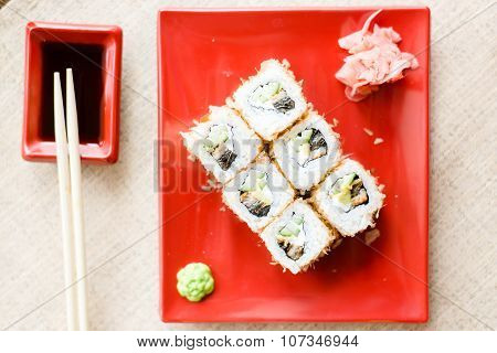Delicious sushi with wasabi and ginger on red plate