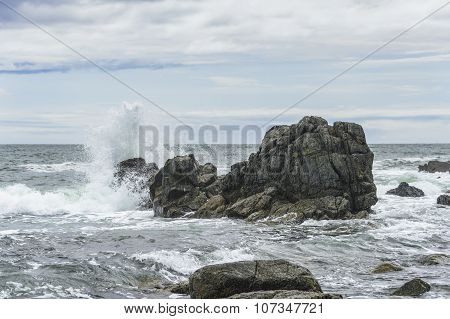 Waves breaking on the rocks .