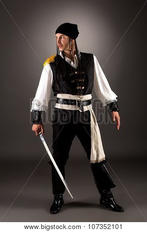 Daring pirate with saber. Photo on gray background