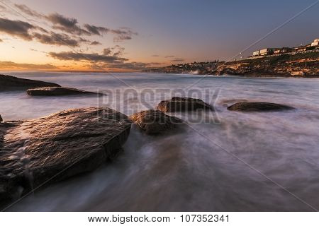 Sunrise Seascape With Rocks And Flowing Water On Long Exposure And Houses