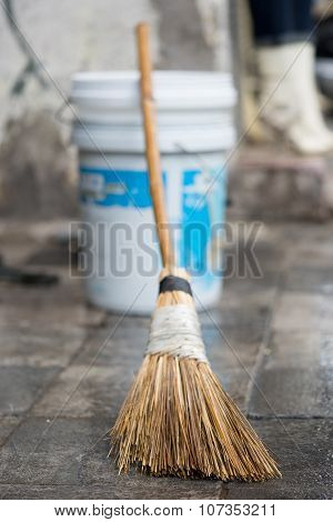 Close up of a bamboo broom and a plastic can