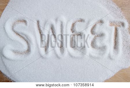 The Word Sweet Written Into A Pile Of White Granulated Sugar Background