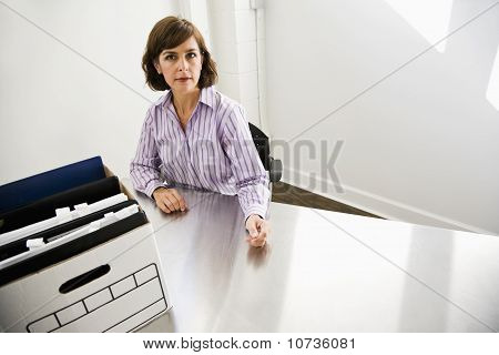 Office Worker Sitting At Table With Box Of Files