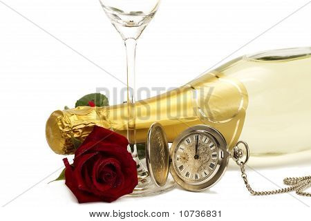 wet red rose under a champagne bottle with a old pocket watch and a empty champagne glass