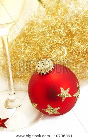 Red christmas ball from top with angels hair and a champagne glass