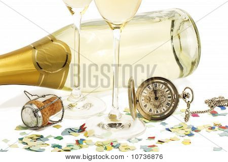 two glasses with champagne, old pocket watch, cork and confetti in front of a champagne bottle