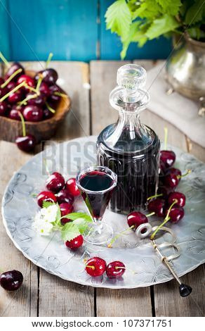 Cherry homemade liquor in a vintage bottle with fresh cherries.