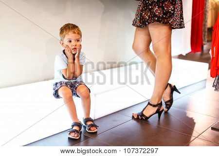 Bored boy sitting in the store while woman buy clothes rack in the background