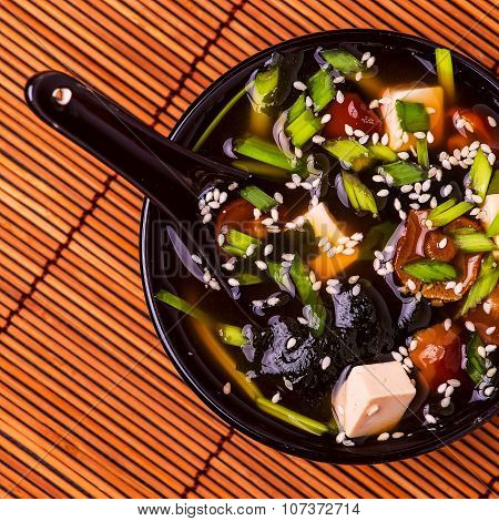 Japanese Miso Soup In A Black Bowl On Bamboo Napkin.