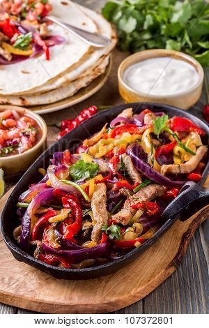 Pork Fajitas With Onions And Colored Pepper, Served With Tortillas, Salsa And Sour Cream.