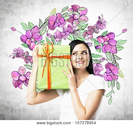 A Curious Brunette Woman Tries To Guess What Is Inside The Green Gift Box. The Sketch Of Purple Flow