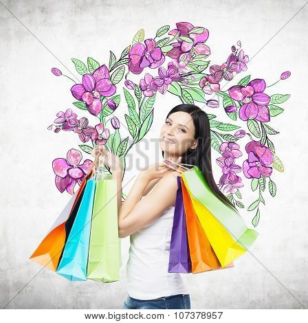 A Happy Brunette Woman Holds Colourful Bags From Fancy Shops. The Concept Of Shopping. A Sketch Of P