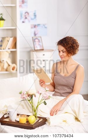 Nice girl having breakfast in bed