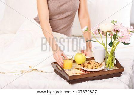 Nice girl having breakfast in bed
