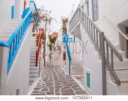 Mykonos town streetview with stairs and blue and grey and red banisters, Greece