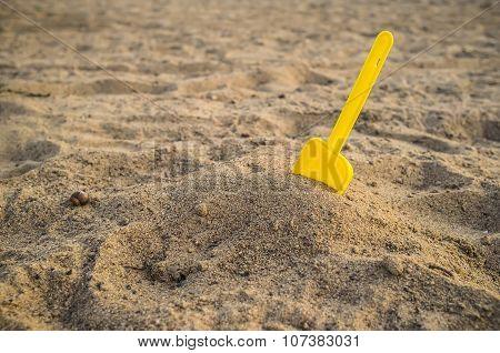 Children's yellow shovel on the beach