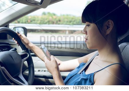 Woman Driver Using A Smart Phone In Car
