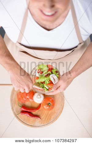 Smiling strong man is mixing a salad.