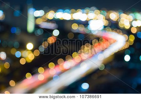 Abstract blurred bokeh lights city downtown highway road curved at night