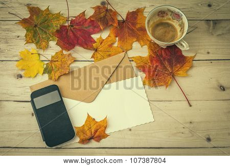 Cup Of Coffee With Smartphone And Letter Decorated With Autumn Leaves
