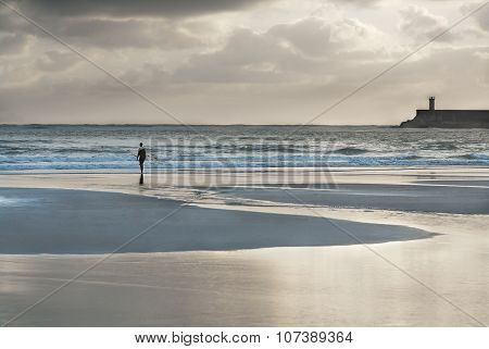 Surfer walking  to the sea at sunset