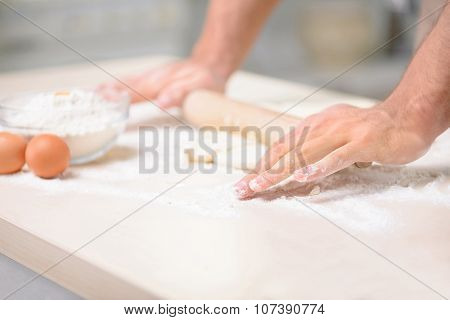 Young male cook is stretching the dough thoroughly.