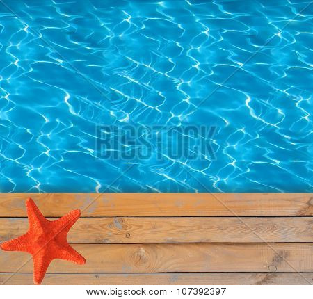Swimming Pool With Blue Clear Water And Wooden Deck With Red Star-fish