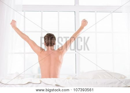 Young man sits on bed and stretches his back.