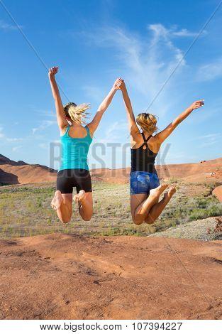 Two Girls Jumping For Joy In The Desert