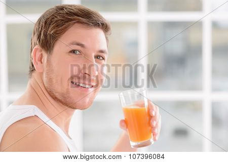 Young handsome guy enjoys a glass of juice.