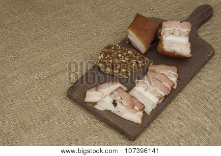 Cutting board with smoked bacon and bread. Raw bacon