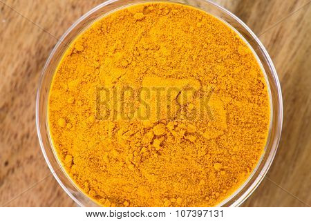 The powder of turmeric in the glass bowl on the wooden background
