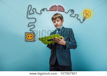 Teenage boy in a suit holding a tablet charging cord plug wire i