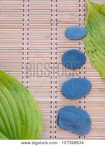 Two Green Leaves And Four Gray Stones On The Bamboo Mat