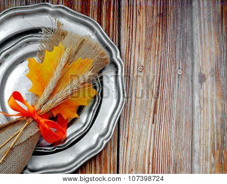 A rustic place setting with maple leaf and wheat decorations on rough wooden background. Old pewter plates, stained silver-plated flatware with a burlap napkin tied with a bright orange ribbon.