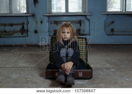 Depressed girl sitting in suitcase
