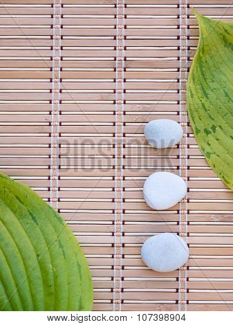Two Green Leaves And Three White Stones On The Bamboo Mat