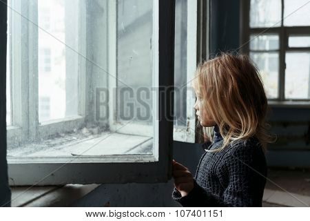 Depressed poot girl standing near window