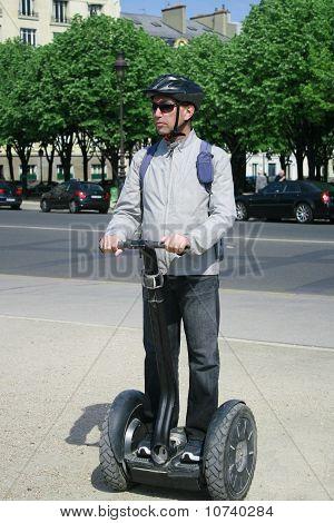 A Man Riding A Segway Machine In Paris
