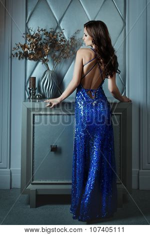 Woman  Dress With  Bare Back Standing In A Dark Room.