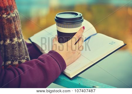 Hands Holding Cup And Book