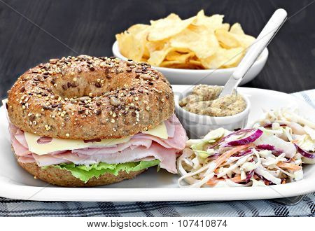 Bagel Ham, Cheese And Lettuce Sandwich With A Side A Spicy Mustard And Coleslaw.