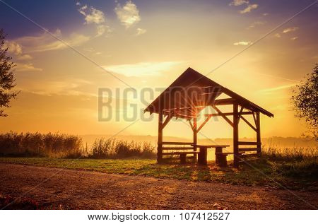 Wooden shelter on the lake at sunrise.