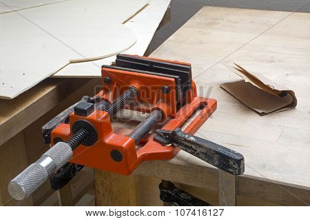 Old Table Vise In Orange With Dust And Rust On A Home Workbench