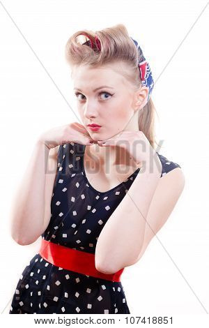 Pinup young woman in polka dot dress and victory rolls