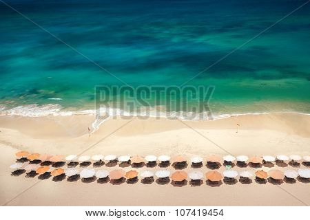 An overhead view of beach chairs set up on a Bali beach in the morning.