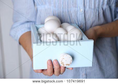 Eggs in basket in women hands on wooden background