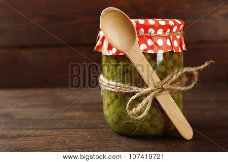 Glass jar of preserved peas on wooden background