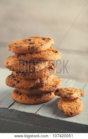 Cookies with chocolate crumbs on blue wooden table against blurred background, close up