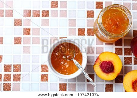 Tasty jam in the jar and bowl, ripe peaches on mosaic background close-up